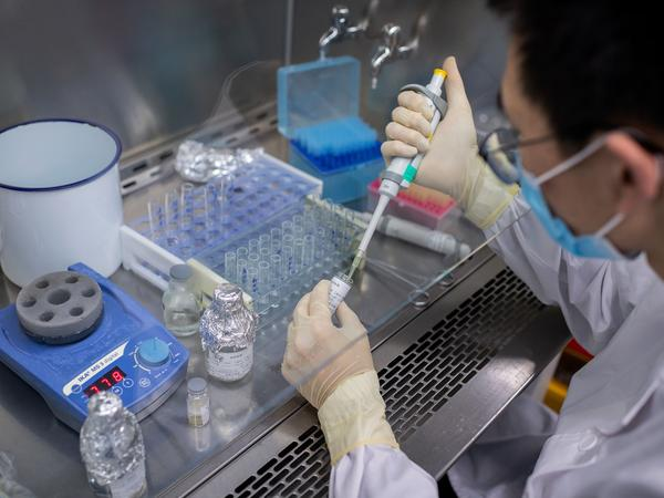 An engineer works in April on an experimental COVID-19 vaccine at Sinovac Biotech's facilities in Beijing. Sinovac Biotech is conducting one of four clinical trials that have been authorized in China.