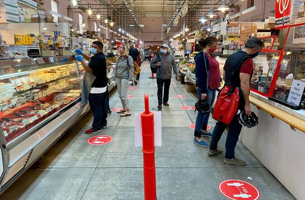 Shoppers wear masks at Eastern Market in Washington, D.C., on May 17. An NPR/<em>PBS NewsHour/</em>Marist poll finds that most Americans think it will take at least six months to return to normal daily life.