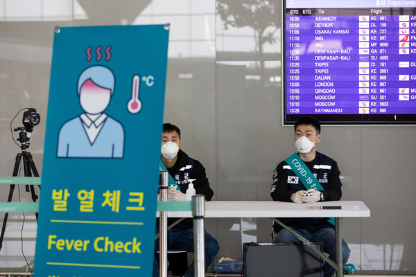 South Korean soldiers wearing protective masks sit at a temperature screening point at Incheon International Airport, South Korea, on March 9.