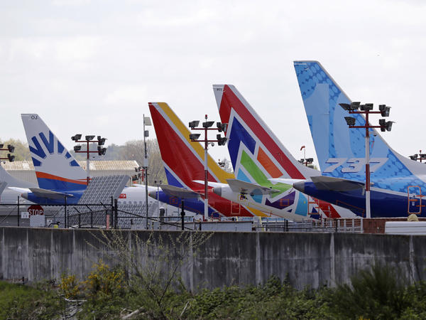 A line of Boeing 737 MAX jets sit parked on the airfield adjacent to a Boeing production plant last month in Renton, Wash. Boeing now says it is cutting thousands of jobs.