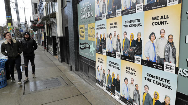 People walk past posters encouraging participation in the 2020 census in April in Seattle. A group of House Democrats have introduced a bill that would grant the U.S. Census Bureau's request to delay major deadlines for delivering results of the count because of the pandemic.