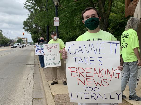 SJ-R Reporter Brenden Moore displays a sign as he and other colleagues protest a decision by paper owner Gannett to change the print deadline on May 27.