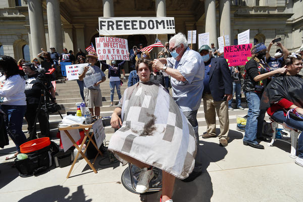 Barber Karl Manke, of Owosso, Mich., gives a free haircut to Parker Shonts on May 20 on the steps of the State Capitol. On Thursday, the Michigan Court of Appeals says Manke must close his barbershop.