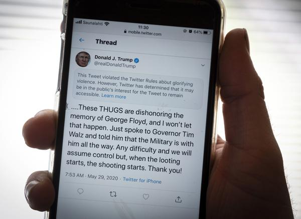 "President Trump's Twitter page is displayed on a mobile phone. The social media company flagged one of his tweets about Minneapolis as ""glorifying violence"" and hid it from public view unless a user clicks on it."