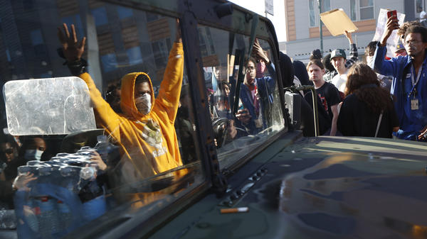 "A National Guard vehicle reflects a crowd of protesters Friday in Minneapolis, where Maj. Gen. Jon Jensen said that night's deployment ""was not enough"" to handle the massive protests over the death of George Floyd."
