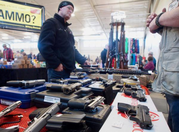 Gun show promoter Ramon Amoureux, right, talks to a customer at a gun show in Caldwell, Idaho, in this 2019 file photo.