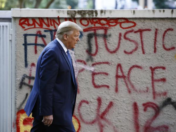 President Trump walks past protest graffiti in Lafayette Park, near the White House, on his way to visit St. John's Church on Monday.