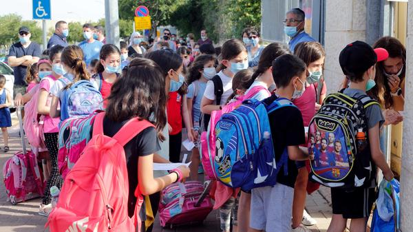 Students wear masks May 17 outside a school in the Israeli city of Modiin. Israeli students in all grades went back to school last month.
