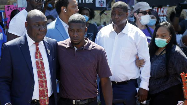 All four former Minneapolis police officers connected with George Floyd's death now face criminal charges. Attorney Ben Crump (left) escorts Floyd's son, Quincy Mason Floyd (second from left), on Wednesday during a visit to the memorial at the site where George Floyd was arrested in Minneapolis.
