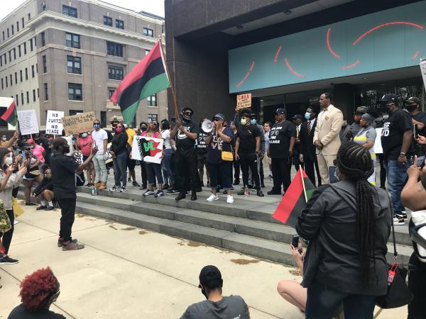 Protesters began to gather at the front of Dayton's Federal Building around 11:30 a.m., filling the lawn and sidewalk areas.