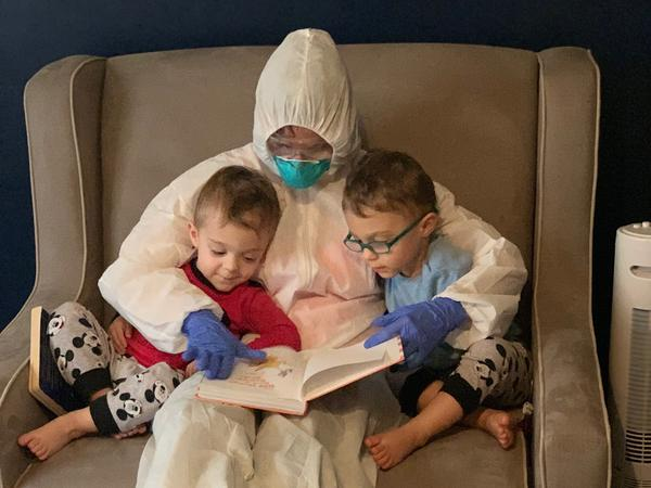 "Dr. Lauren Jenkins reads to her twin sons, Pierce and Ashton, while wearing her ""hazmat"" suit. Because lung cancer has compromised her husband's immune system, Jenkins moved out of her home and visited in the suit as a precaution."