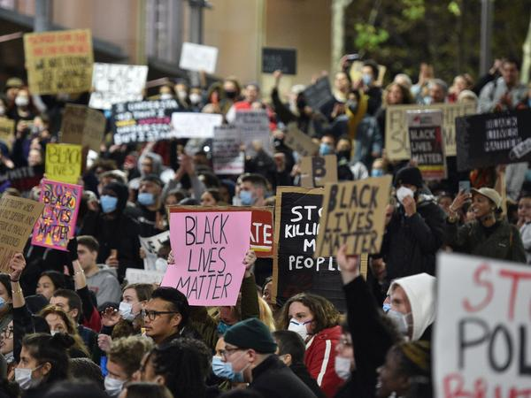 """Marchers shout slogans and hold up placards Tuesday during a """"rally for justice"""" in Sydney, protesting the deaths of members of the Aboriginal community in Australia and the death of George Floyd, an unarmed black man who died in police custody in Minneapolis. Minn."""