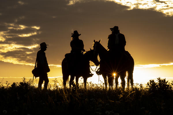 On a hill of prairie grasses near Easton, Kansas, Gregory Mayse (at left) speaks to a group of riders as the sun sinks beneath the horizon. Mayse is a Western and wildlife artist from Fort Collins, Colorado, who has come to gather material for paintings.