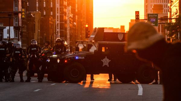 Police officers take guard during a protest over the death of George Floyd last month in Minneapolis.