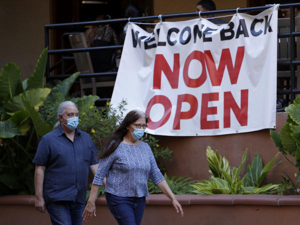 Visitors to the River Walk in San Antonio pass a reopened restaurant on May 18. Texas Gov. Greg Abbott says bars and bowling alleys are on the list of businesses that can reopen at 25% beginning Friday, and restaurants can increase to 50% capacity as the state continues to go through phases to reopen.