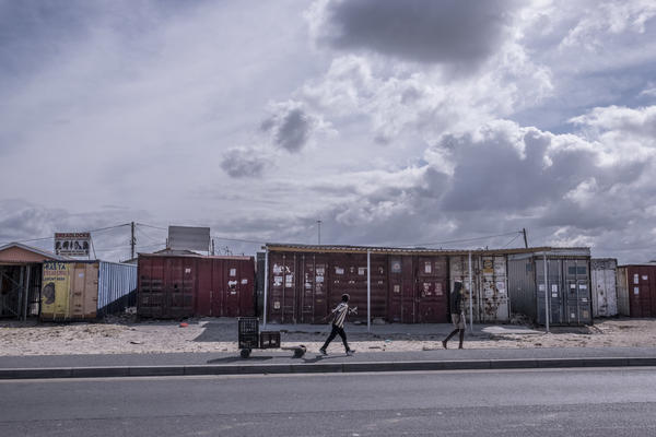Boys walk past shuttered businesses in the township of Khayelitsha in Cape Town, South Africa, during the coronavirus lockdown. This recession is the first triggered solely by a pandemic, and low-income countries are particularly hard-hit.