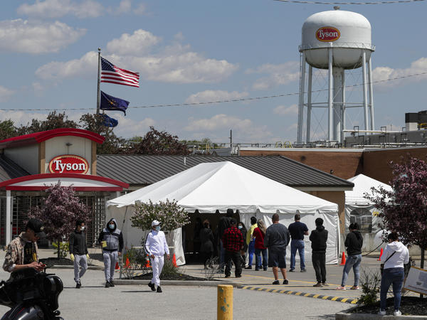 Workers line up to enter a Tyson Foods pork processing plant last month in Logansport, Ind. Some of the worst workplace coronavirus outbreaks have been in the meatpacking industry. Major meatpackers JBS USA, Smithfield Foods and Tyson have said worker safety is their highest priority.