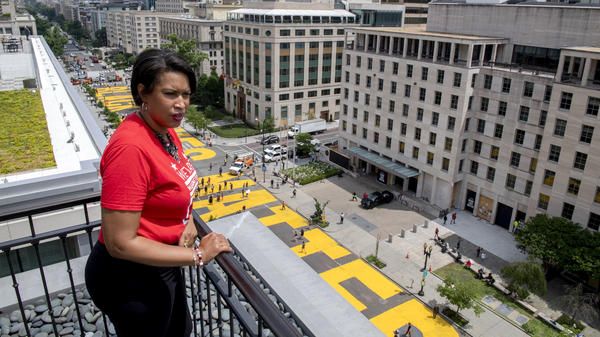 "Mayor Muriel Bowser stands on the rooftop of the Hay-Adams Hotel near the White House and looks out at the words ""Black Lives Matter"" that have been painted in bright yellow letters on the street."