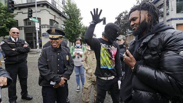"Seattle Police Chief Carmen Best (second from left) talks this week with activists Raz Simone (right) and Keith Brown near the spot in the ""Capitol Hill Autonomous Zone"" where police had earlier boarded up a precinct building."