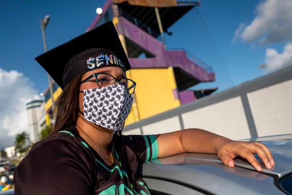 A graduating student from the Ramon Power Y Giralt High School attends a symbolic graduation from inside her car to maintain social distance at a parking lot in Las Piedras, Puerto Rico, on May 13, 2020. (RICARDO ARDUENGO/AFP via Getty Images)