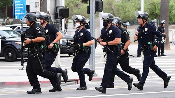 Los Angeles police officers run to formation during a protest on June 1.