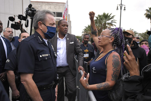 Los Angeles Police Department Chief Michel Moore speaks to a protester after a vigil with members of professional associations and the interfaith community at LAPD headquarters, Friday, June 5, 2020, in Los Angeles.