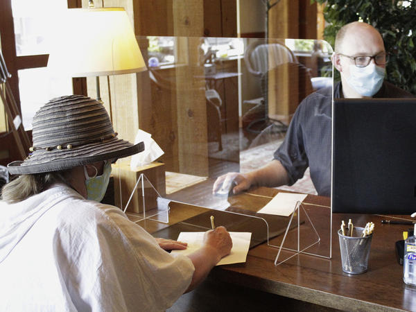 A hotel employee helps a guest from behind protective plastic last month at the Ocean Lodge in Cannon Beach, Ore.