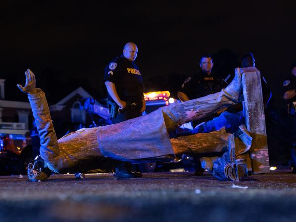 A statue of Confederate States President Jefferson Davis lies on the street after protesters pulled it down in Richmond, Va., on Wednesday.
