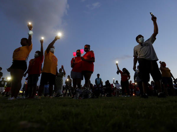 Local residents take part in a candle light vigil to honor George Floyd in Houston, Monday, June 8, 2020, in Houston.