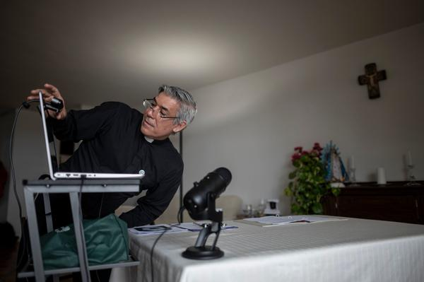 Fabian Arias, a Lutheran pastor with Saint Peter's Church in Manhattan, prepares his Sunday services via internet live stream on May 24, 2020 in the streets in Harlem neighbourhood of Manhattan in New York. (JOHANNES EISELE/AFP via Getty Images)
