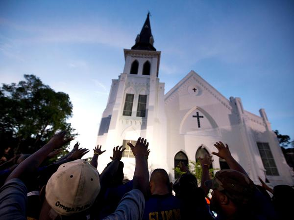 In this June 19, 2015, file photo, the men of Omega Psi Phi Fraternity Inc. lead a crowd of people in prayer outside the Emanuel AME Church, after a memorial service for the nine people killed by Dylann Roof in Charleston, S.C.