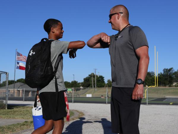 Football coach Bob Wager (right) and sophomore safety Cameron Conley greet each other Thursday at the reopening of strength and conditioning camp at Martin High School in Arlington, Texas. State officials say they plan to open schools for in-person instruction in the fall.
