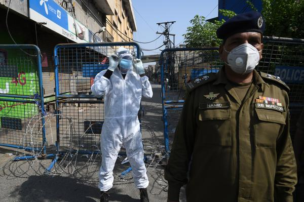 A policeman guards a street sealed by the authorities at a residential area in Lahore on June 17 as COVID-19 cases continue to rise.