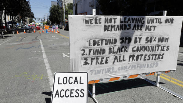 "The Seattle Police Department will return to their East Precinct building ""in the near future,"" Mayor Jenny Durkan says. Here, a sign on a street barricade lists protesters' demands in the Capitol Hill Occupied Protest zone, where two shootings took place over the weekend."