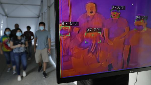 Texas is reporting an all-time high in new COVID-19 cases, Gov. Greg Abbott says. Here, visitors to Six Flags Fiesta Texas in San Antonio pass through a thermal screening area Friday. The park opened at 50% capacity.