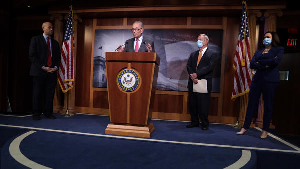 Senate Minority Leader Chuck Schumer, D-N.Y., speaks as Sen. Cory Booker, D-N.J., Senate Minority Whip Dick Durbin, D-Ill., and Sen. Kamala Harris, D-Calif., listen at a news conference Tuesday criticizing GOP leaders for failing to agree to bipartisan talks on police reform. Republicans say Democrats should advance the GOP bill and propose changes.
