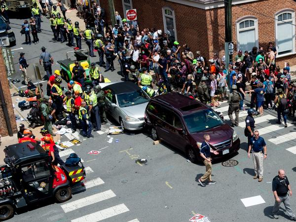 People receive first-aid after a car ran into a crowd of protesters in Charlottesville, Va. on August 12, 2017. This photo appropriately replaced the original photo selected for the story.