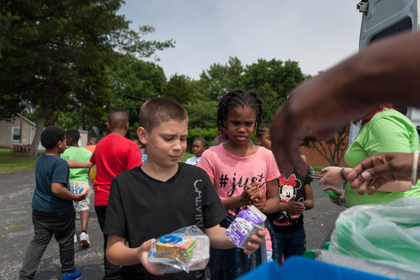 A child picks up lunch during a summer meal program in June 2018. Government aid to make up for lost school meals this spring hasn't reached all needy families.