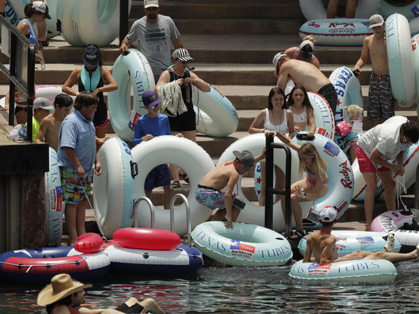 """Tubers prepare to float the Comal River in New Braunfels, Texas, on Thursday. Texas Gov. Greg Abbott said Wednesday that the state is facing a """"massive outbreak"""" of the coronavirus and that some new local restrictions may be needed to preserve hospital space for new patients."""