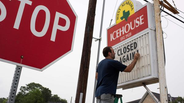 "Bar owner Petros J Markantonis changes the marquee outside his bar to ""Closed Again"" at the West Alabama Ice House in Houston."