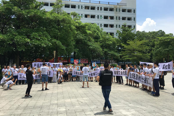People hold banners at a demonstration in support of Jasic Technology factory workers, outside Yanziling police station in Pingshan district, Shenzhen, Guangdong province, China, on Aug. 6, 2018.