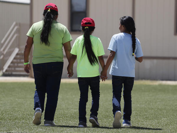 Immigrants seeking asylum hold hands last year at the ICE South Texas Family Residential Center in Dilley, Texas. Independent inspectors told a judge that tests for the coronavirus at such centers and the infection rates in the counties where the Texas facilities are located are cause for concern.