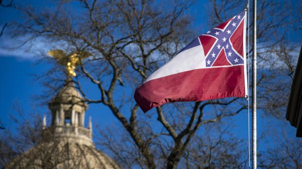 The Mississippi state flag flies in front of the capitol dome in 2019. Lawmakers have voted to remove and replace the flag.