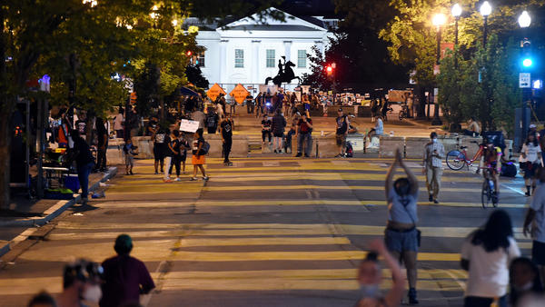 Protesters gather on Friday night at Black Lives Matter Plaza in front of the White House and the statue of former President Andrew Jackson, which is protected by a fence and concrete blocks.