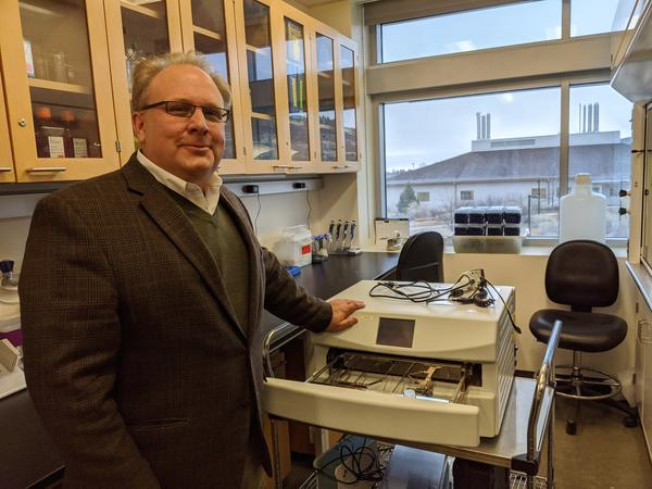 Ray Goodrich, director of the Infectious Disease Research Center at Colorado State University, stands next to the portable device that is used to create the key ingredient in their COVID-19 vaccine candidate.