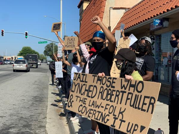 Protestors spurred by the death of Robert Fuller signal cars who honk in support on a busy street in Palmdale, California.