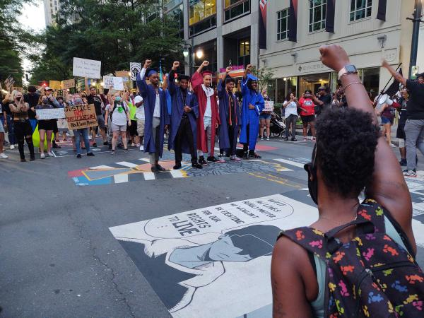 A group of graduates poses next to the Black Lives Matter street mural as protesters gather around and shout encouragement on Friday, June 12.