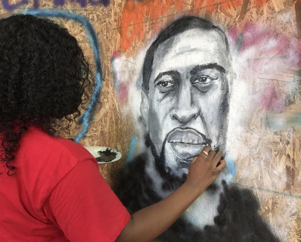 Kalli Moore paints a portrait of George Floyd on a board that had been put in front of a business on South Tryon Street in uptown Charlotte on June 11.