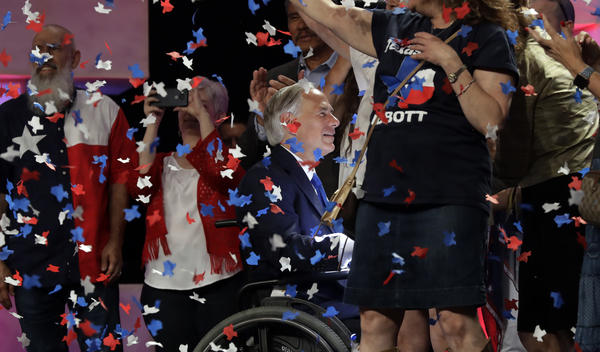 Confetti falls as Texas Gov. Greg Abbott, center, greets supporters after speaking at the 2018 Texas GOP Convention in San Antonio.