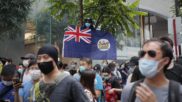 A man displays the Hong Kong colonial flag Wednesday, the anniversary of the city's handover to China from Britain in 1997. The gesture could be prosecuted under Beijing's new national security law, which it imposed on Hong Kong.